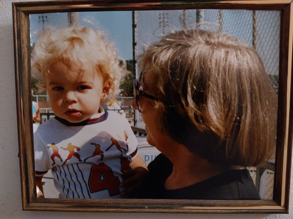 Me as a toddler. I have curly blond hair. My late grandmother holding me up at a baseball field in the stands.