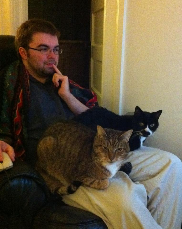 Me sitting on a lazy boy chair with cats Flip (left), and Tip (right) sitting on the chair arms.