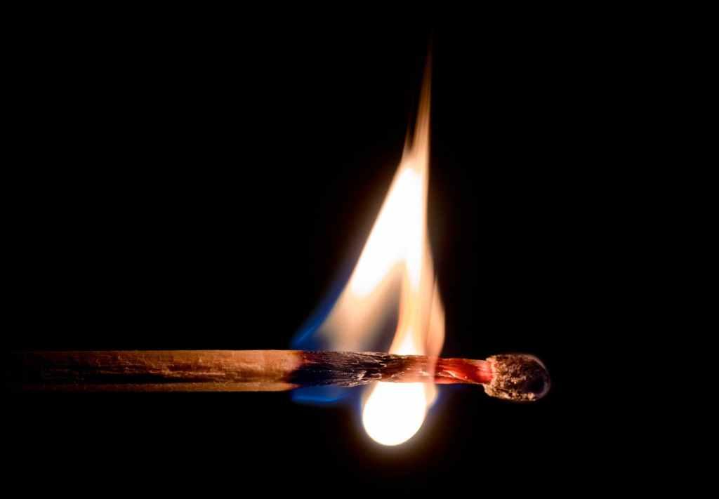 A lit match burning through.