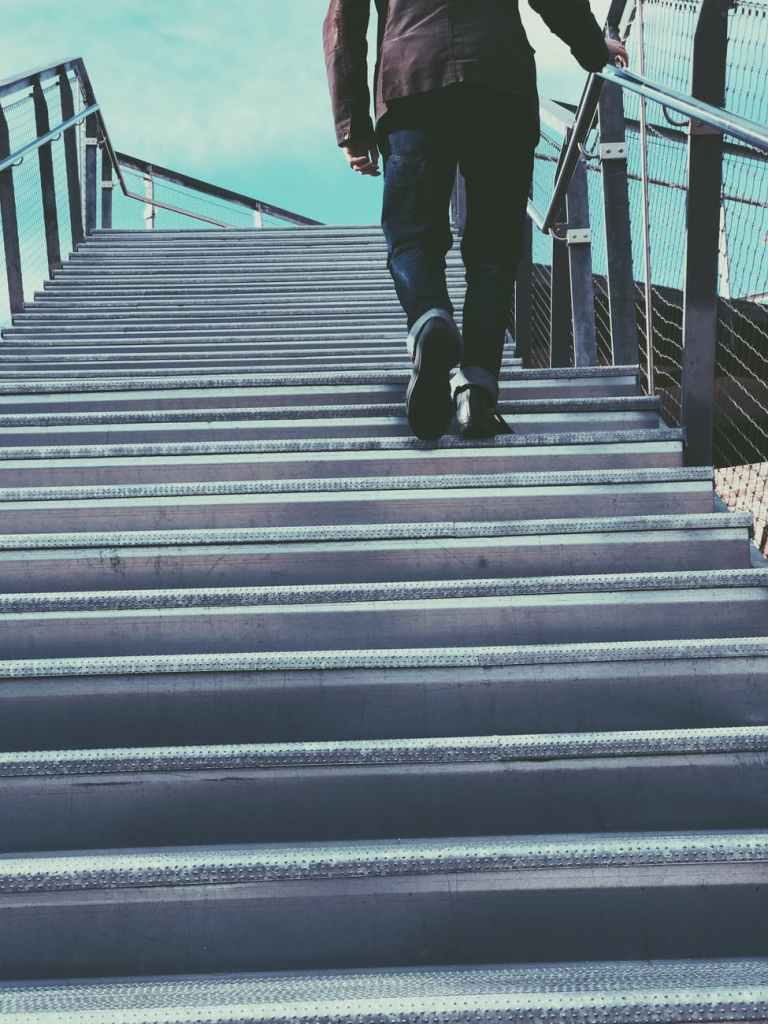 Man outside waking stairs to a bridge