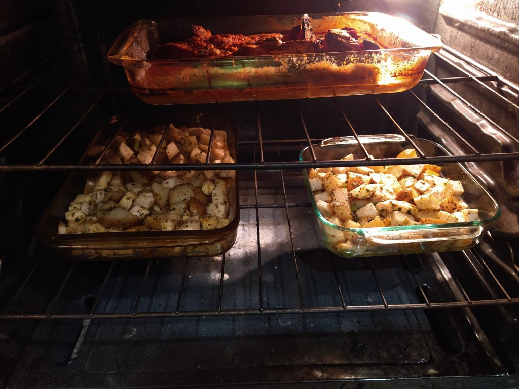 Picture of an oven with a pan of simmering Jerk Pork, and 2 other glass pans with chopped root vegetables. All roasting at 450 F